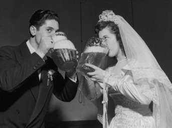 Bride and groom drinking pitchers of beer.