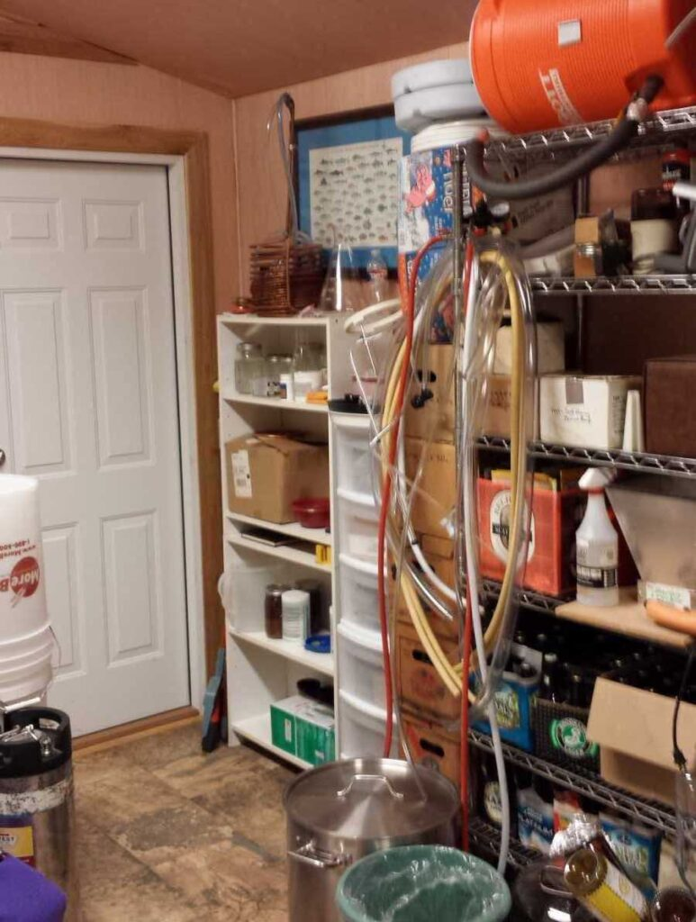 A picture of home brew equipment including hoses, kegs, coolers, etc. on metal racking.