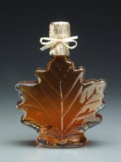An image of maple syrup in a leaf shaped glass bottle