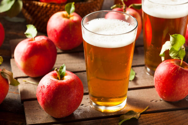 A picture of hard cider in a glass sitting on wooden planks with apples sitting around it.