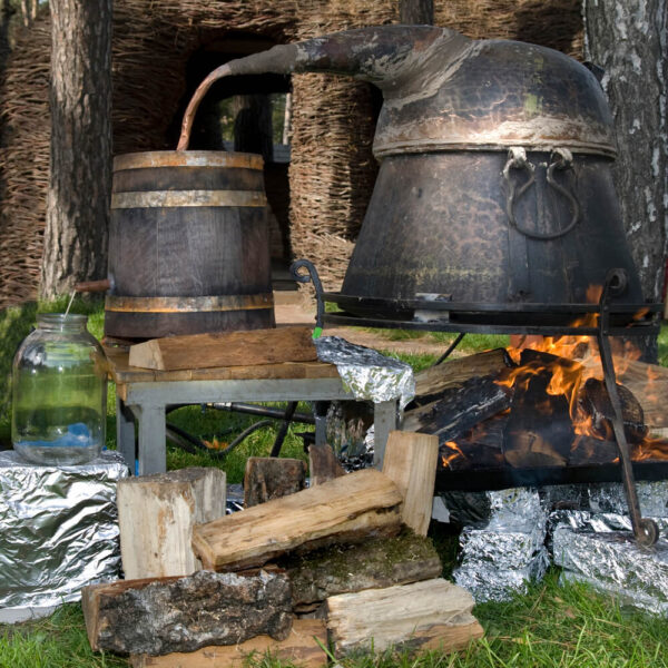 A picture of a making moonshine over a fire with kettles.
