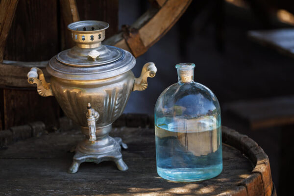 Moonshine in a glass jar on a wooden barrel with a metal dispenser.