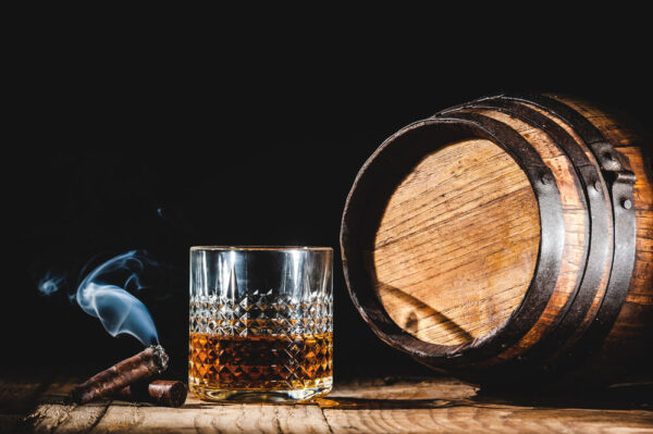 A picture of bourbon in a glass next to a wooden barrel and a smoking cigar.