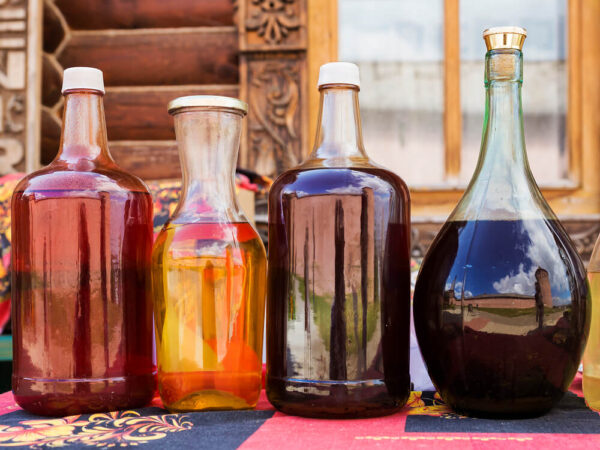 Four bottles of liquor one of which being mead. A window and house in the background.